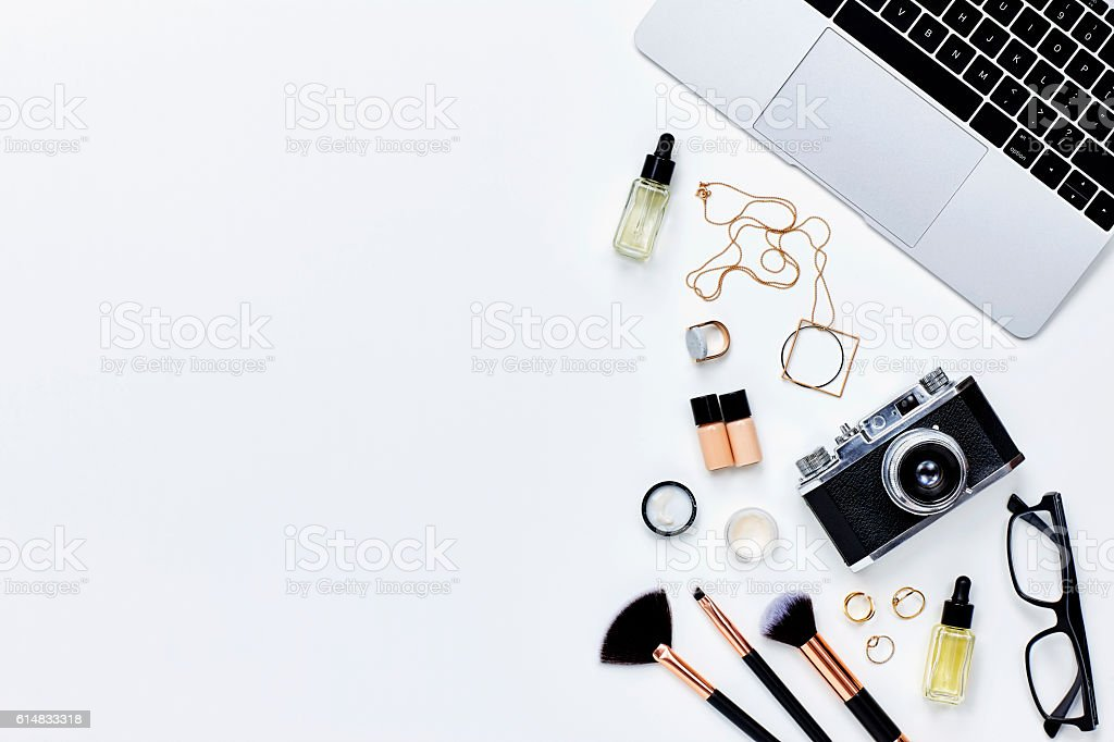 Various beauty products with camera and laptop on white background