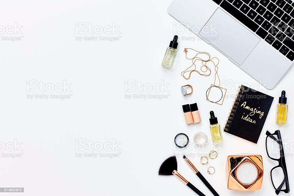 Various beauty products with diary and laptop on white