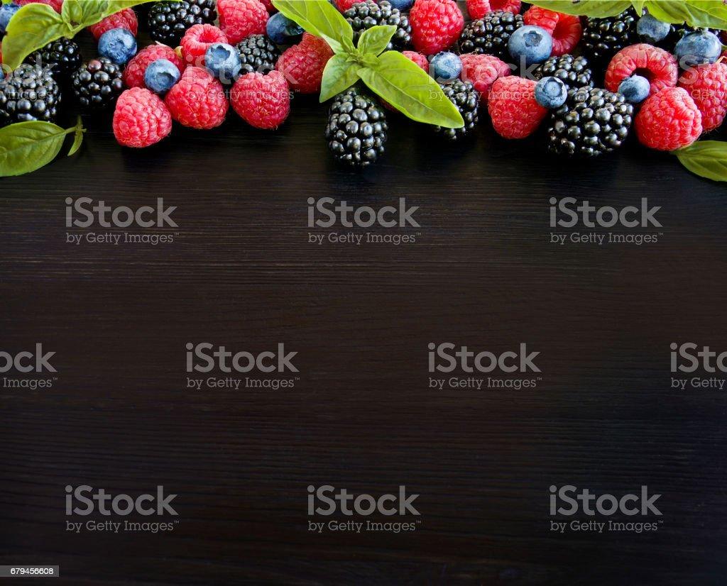 Various berries on a black background. Ripe blueberries, raspberries, blackberries. royalty-free stock photo