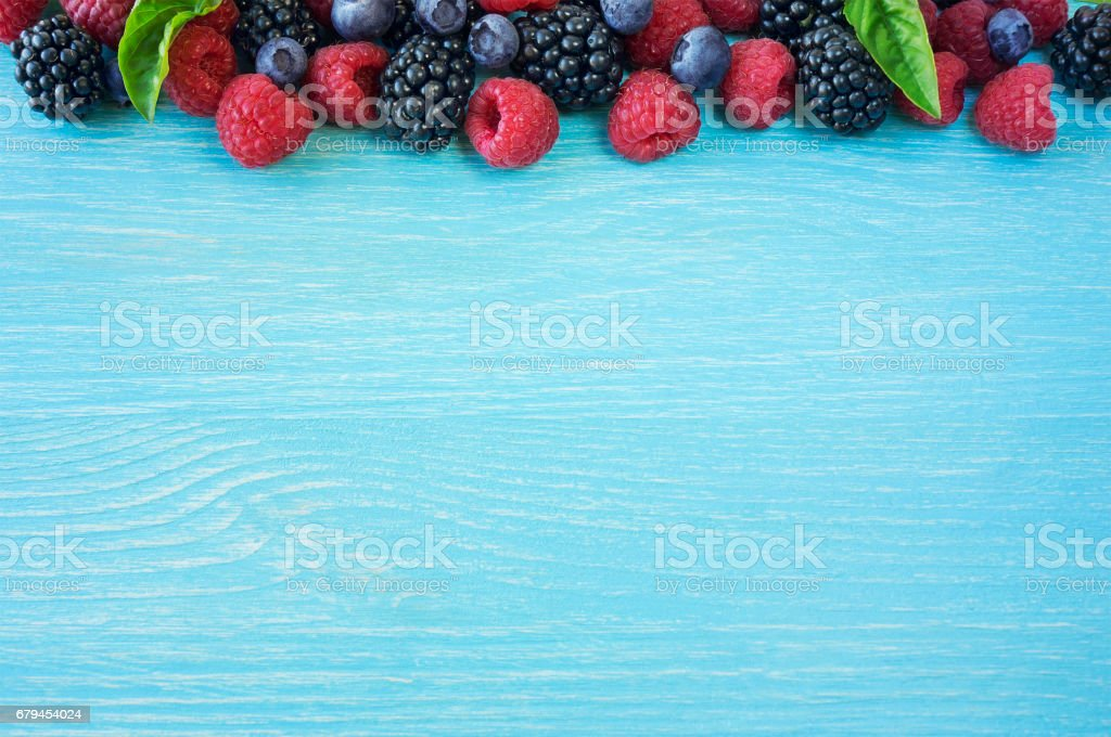 Various berries on wooden background. Ripe blueberry, raspberry and blackberry royalty-free stock photo