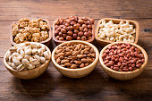 various bowls of nuts on wooden table, top view
