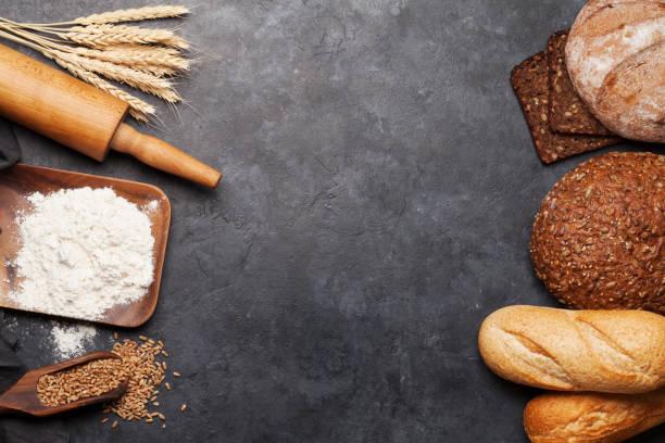 Verschiedenes Brot mit Weizen, Mehl und Kochutensilien – Foto