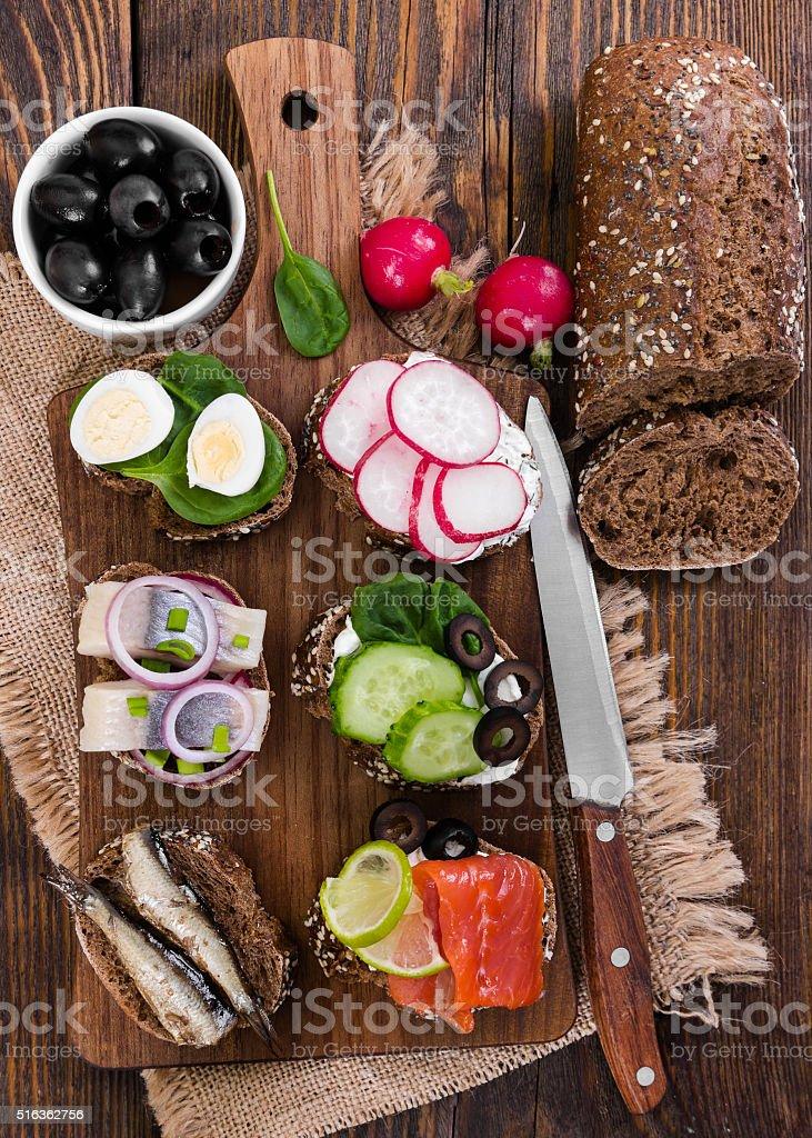 Varios (pan tostado) sobre fondo de madera. - Foto de stock de Aceituna libre de derechos