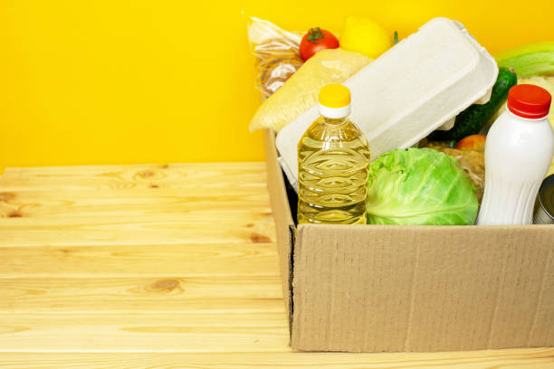 Various canned food, eggs and vegetables in a cardboard box. stock photo