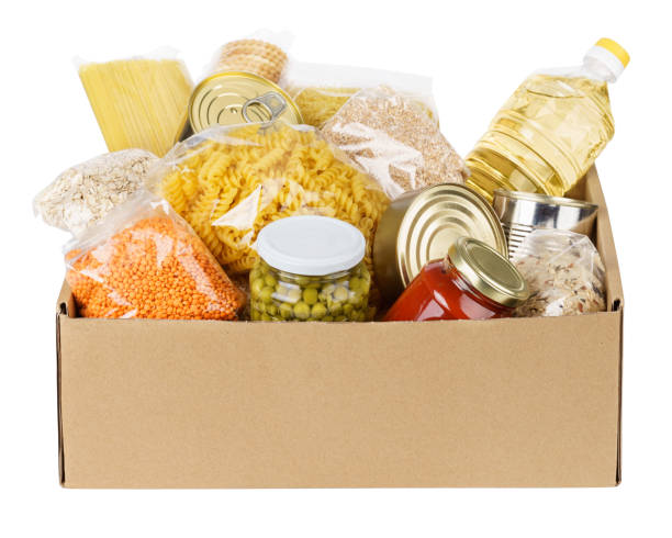 various canned food, pasta and cereals in a cardboard box. - gêneros alimentícios imagens e fotografias de stock