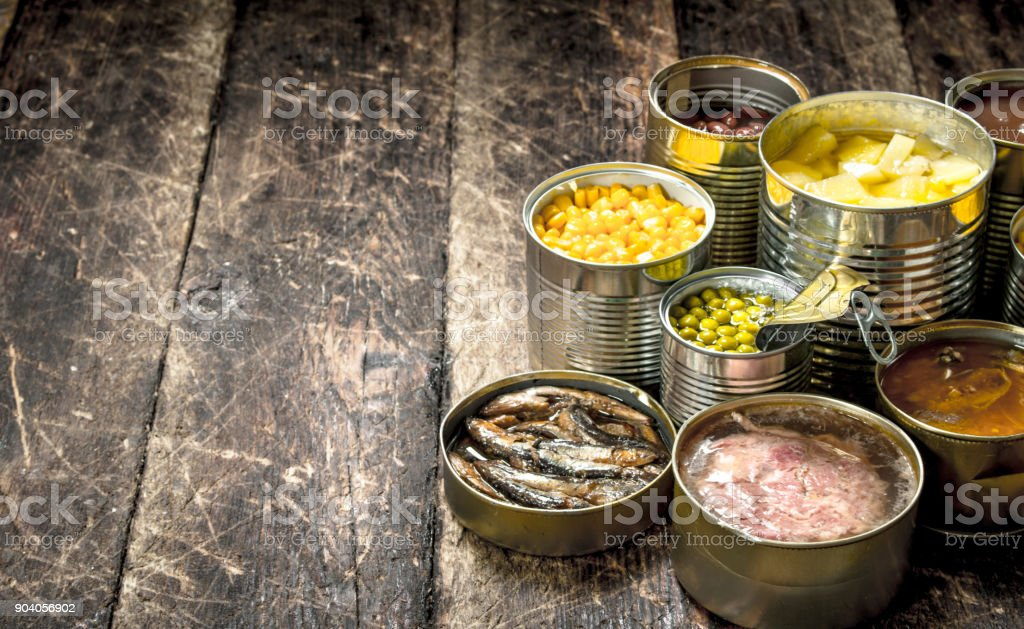 Various canned vegetables, meat, fish and fruits in tin cans. stock photo