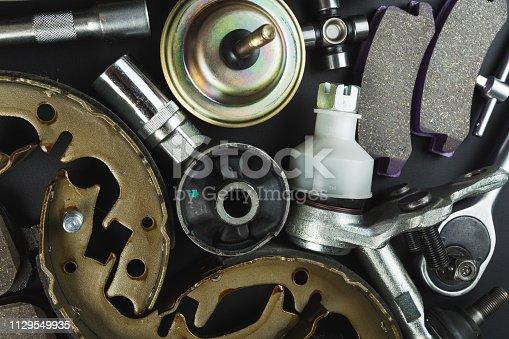 1131085300 istock photo Various Car parts on dark background 1129549935
