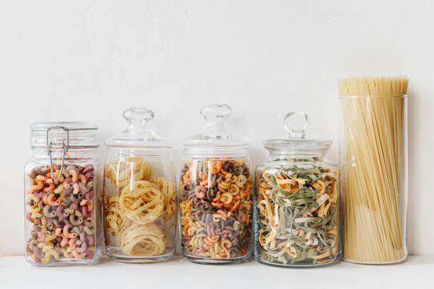 Verschiedene Getreidesorten und Samen in Gläsern auf dem weißen strukturierten Hintergrund. Küche Innenideen. Umweltfreundliche Küche, Null-Abfall-Haus-Konzept – Foto