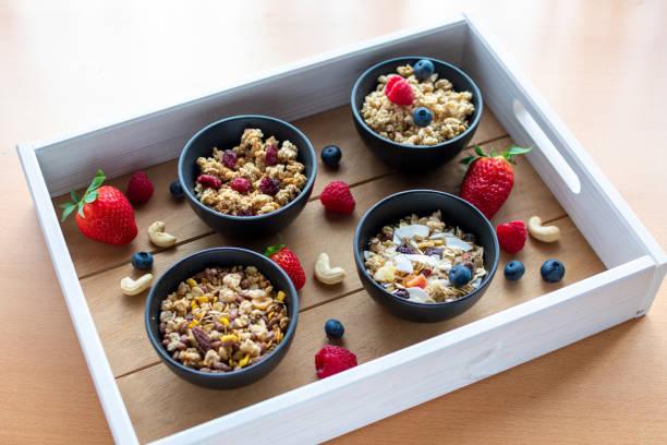 verschiedene Getreidesorten in kleinen Schalen mit frischen und getrockneten Früchten – Foto