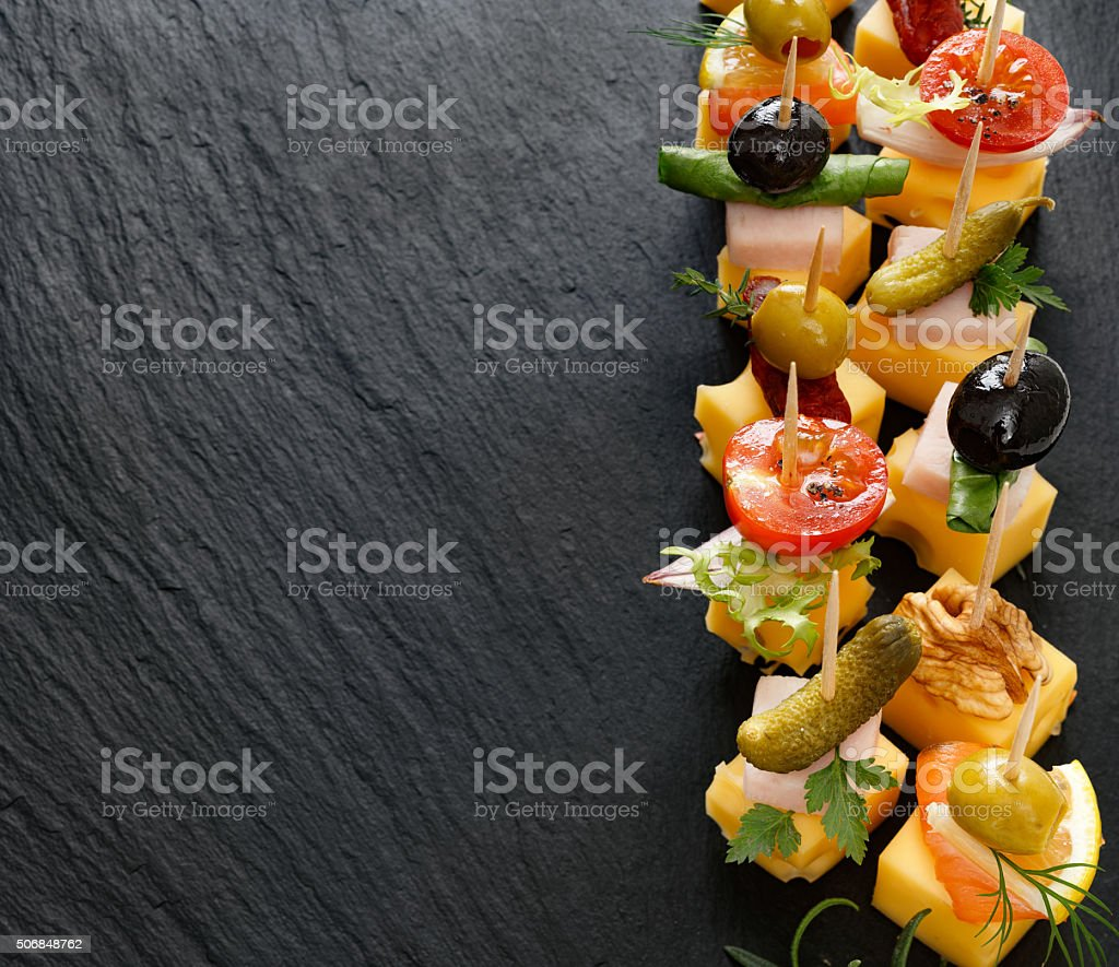 Various cheese skewers  on a stone black background stock photo