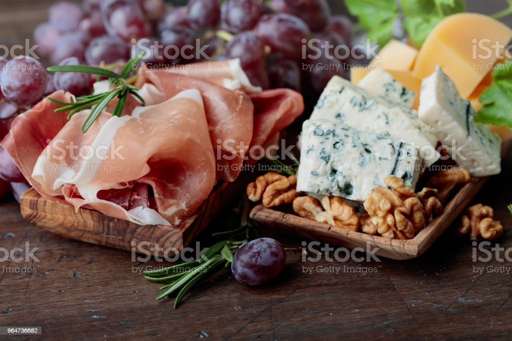Various cheeses , grapes and prosciutto . royalty-free stock photo