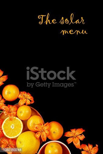 Decorative composition with lily flowers, oranges and mandarines on black background. Flat lay, top view
