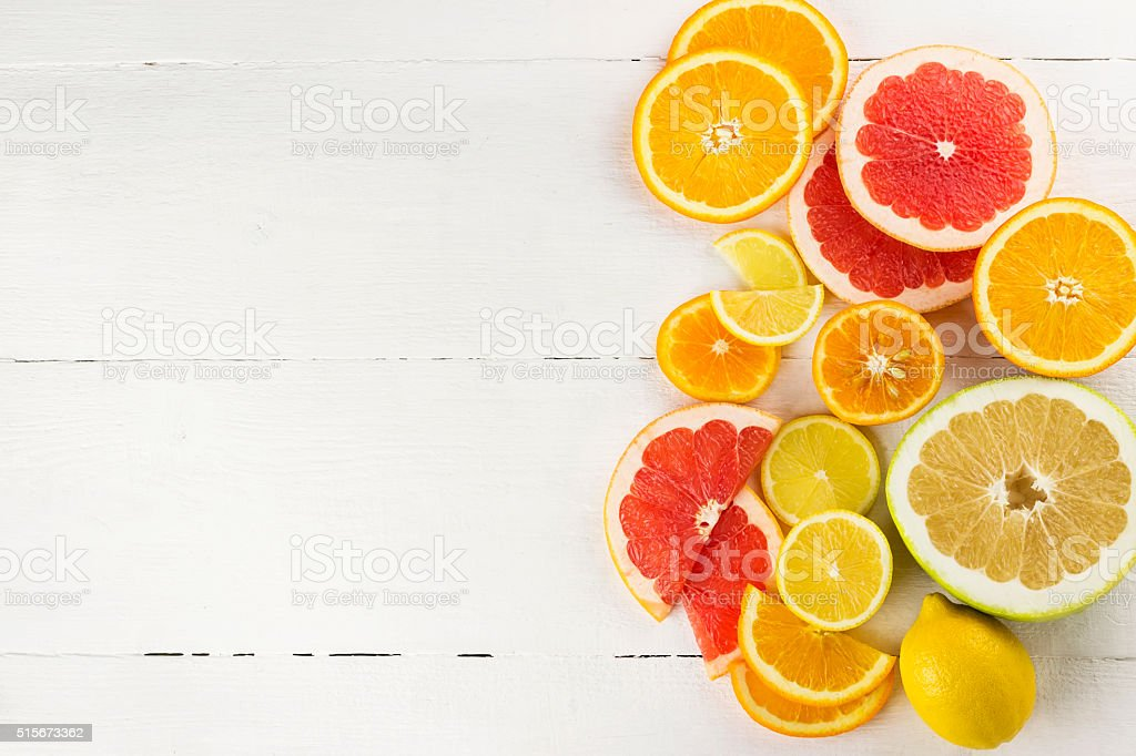 Various citrus on white wooden background stock photo