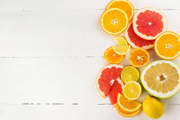 verschiedene zitrus auf weißem holz-hintergrund - zitrusfrucht stock-fotos und bilder