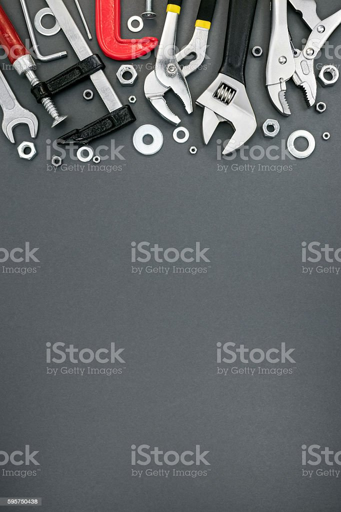 various clamps and adjustable wrenches on grey background stock photo