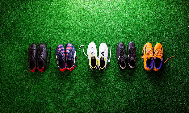 Various cleats against green artificial turf, studio shot Various colorful cleats against artificial turf, studio shot on green background. Flat lay, copy space. studded stock pictures, royalty-free photos & images