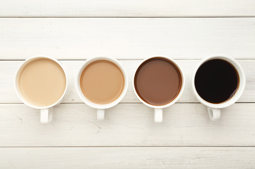 istock Various coffee cups on white wood, top view 941686710