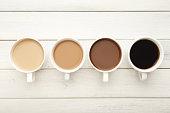 白の木製、トップ ビューでさまざまなコーヒー カップ