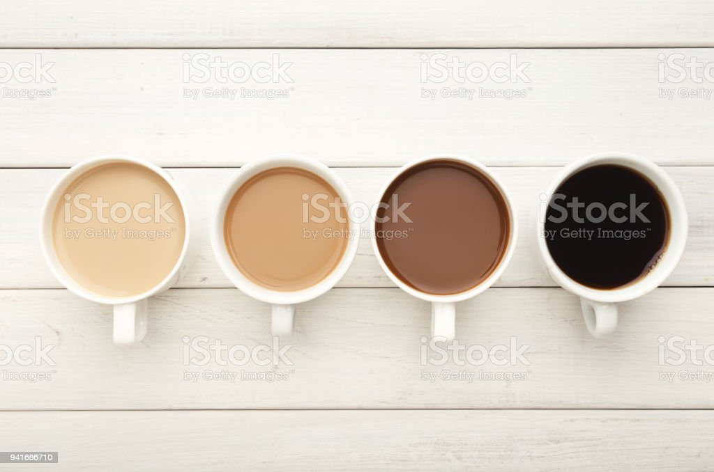 Various coffee cups on white wood, top view stock photo