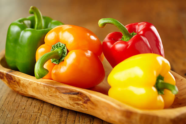 various colorful bell peppers in wooden basket - 椒類 個照片及圖片檔
