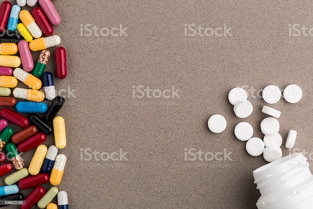 Various colorful capsules and pill bottle from white round pills stock photo