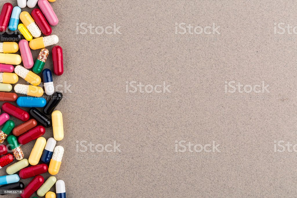 Various colorful capsules and pills on brown craft paper stock photo