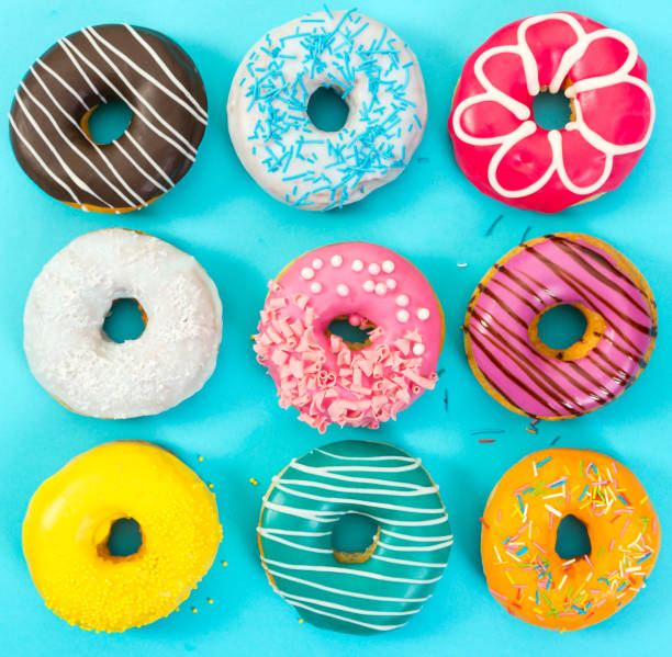 Various colorful donuts on blue background. stock photo