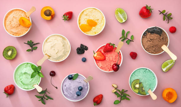 Various colorful ice cream sorts with fruits in paper cups stock photo