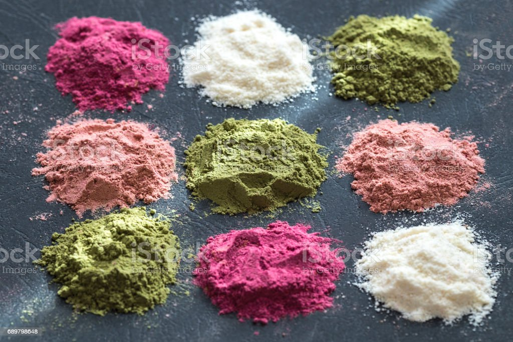 Various colorful superfood powders on dark background. Healthy food supplements, detox concept. Top view stock photo