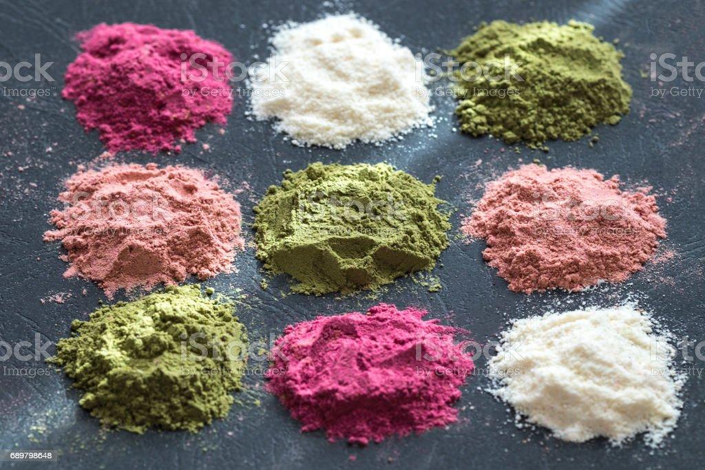 Diverses poudres de super coloré sur fond sombre. Compléments alimentaires sains, detox concept. Vue de dessus - Photo