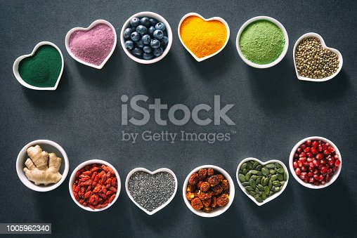 1005962360 istock photo Various colorful superfoods in bowls on dark background 1005962340