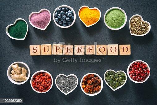 1005962360 istock photo Various colorful superfoods in bowls on dark background 1005962350