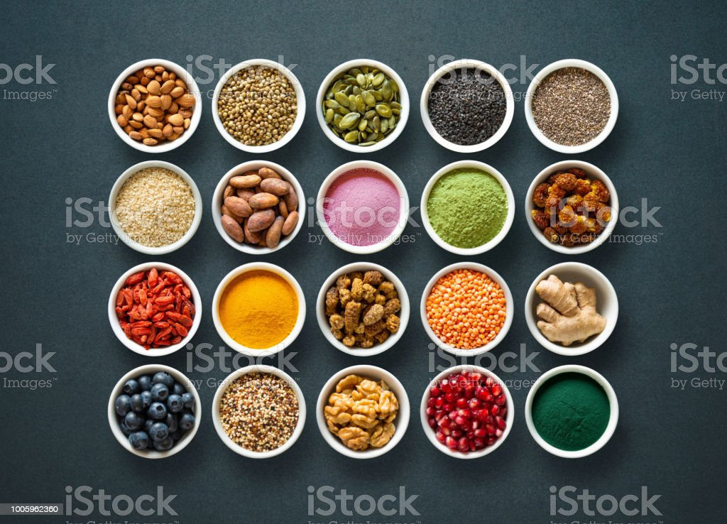Diverse kleurrijke superfoods in kommen op donkere achtergrond - Royalty-free Achtergrond - Thema Stockfoto