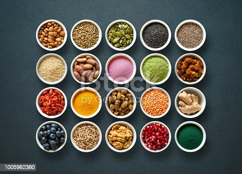 istock Various colorful superfoods in bowls on dark background 1005962360