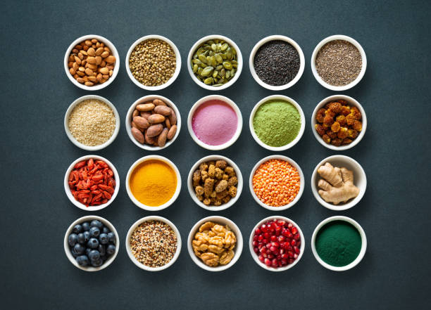 various colorful superfoods in bowls on dark background - antiossidante foto e immagini stock