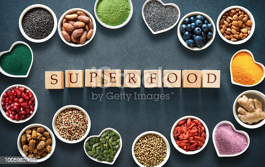 1005962360 istock photo Various colorful superfoods in bowls on dark background 1005962422
