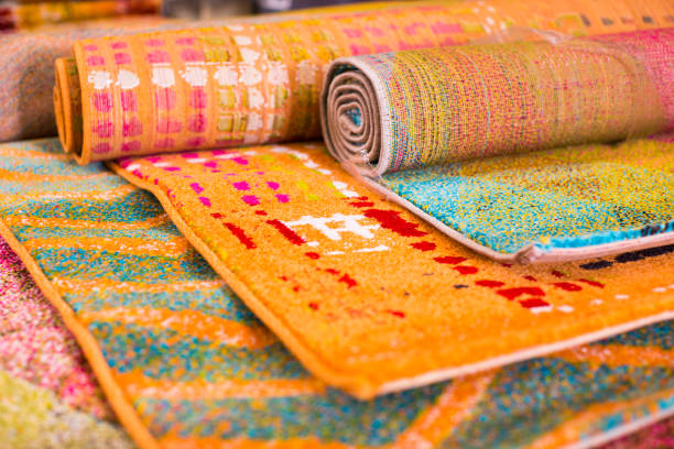 Various colorful wool rugs for sale at store stock photo