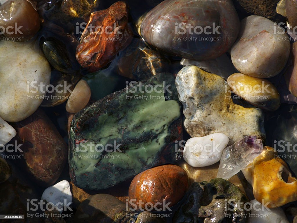 Various coloured rocks on stream bed stock photo