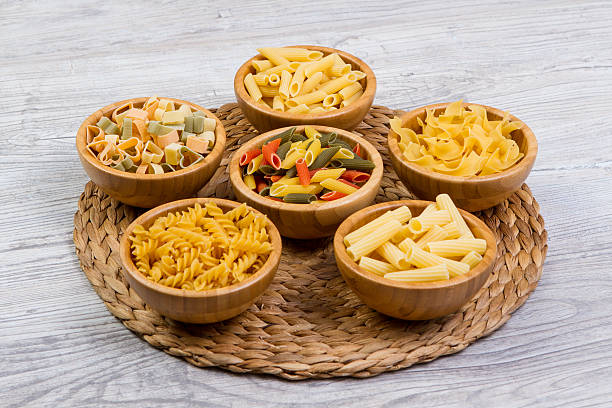 Various combinations of pasta in bamboo bowls on wooden background stock photo