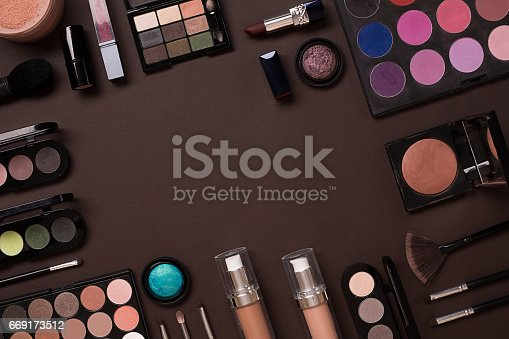 istock Various cosmetics and brushes on brown background 669173512
