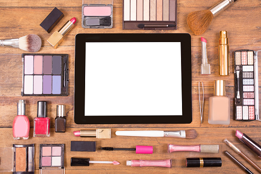 Various cosmetics surround a digital tablet. Dressing table. Knolling.