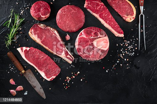 istock Various cuts of meat, shot from the top on a black background with salt, pepper, rosemary and knives, with copy space 1214484853