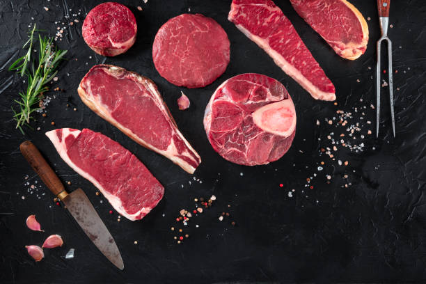 Various cuts of meat, shot from the top on a black background with salt, pepper, rosemary and knives, with copy space Various cuts of meat, shot from the top on a black background with salt, pepper, rosemary and knives, with copy space beef stock pictures, royalty-free photos & images