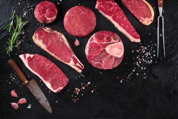 verschiedene fleischstücke, von oben auf schwarzem hintergrund mit salz, pfeffer, rosmarin und messern, mit kopierraum - fleisch stock-fotos und bilder