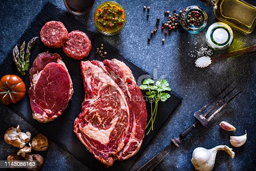 Various cuts of raw meat shot from above on rustic kitchen table. The cuts are on a black slate board and includes Angus steak, tenderloin and hamburger meat. The board is surrounded by herbs, vegetables and spices for cooking meat like peppercorns, salt, garlic, olive oil, tomatoes, asparagus and rosemary. A vintage fork is included in the composition. Predominant colors are red, black and gray. Low key DSRL studio photo taken with Canon EOS 5D Mk II and Canon EF 100mm f/2.8L Macro IS USM.