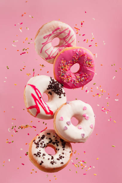 Various decorated doughnuts in motion falling on pink background. stock photo