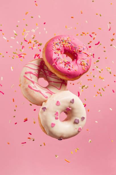 verschiedene dekorierte donuts in bewegung fallen auf rosa hintergrund. - streuselkuchen stock-fotos und bilder