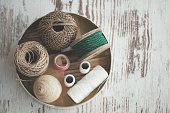 Directly above shot of various decorative ropes in bowl on wooden table, knolling.