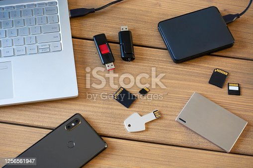 Various digital data storage devices. Usb sticks, external hard drive, SD cards, mini and micro SD cards, laptop and smartphone. Flat lay.