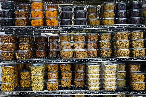 Horizontal shot of a stack of various dried fruit and nuts packaged in airtight transparent plastic containers for convenience and freshness, positioned on a metal rack or shelf at the supermarket
